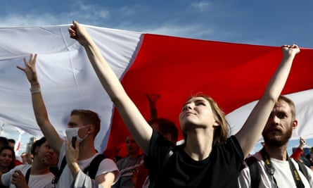 Supporters of the opposition carry a huge flag of the pre-Soviet republic of Belarus