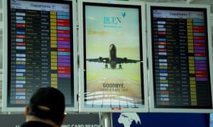 A stranded passengers checks the screens at the departure lounge of Larnaca airport.