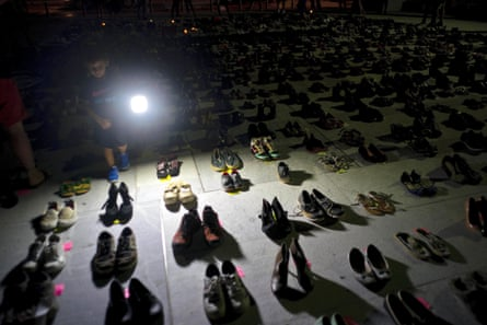A child shines a light on hundreds of shoes at a memorial for those killed by Hurricane Maria.
