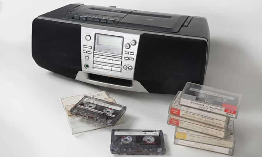 Home recorded cassette tapes stacked up in front of a 1990s style cassette, radio and and CD player.