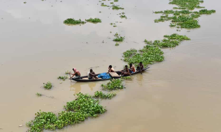 Indian villagers paddle a boat in the flood-affected Morigoan district in July last year. The relentless warming has highlighted the steep challenges faced by governments.
