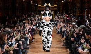 Person in a cow costume models a bag at the Stella McCartney show in Paris