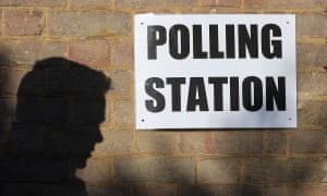 A man enters a polling station as voting begins in local government elections in London