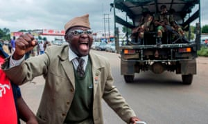 A man cheers as a military vehicle drives past him during a rally in Harare to demand the resignation of Robert Mugabe