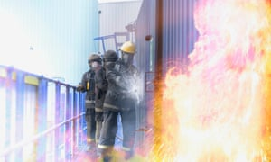 Three firefighters tackling flames in fire simulation at training facility, front view