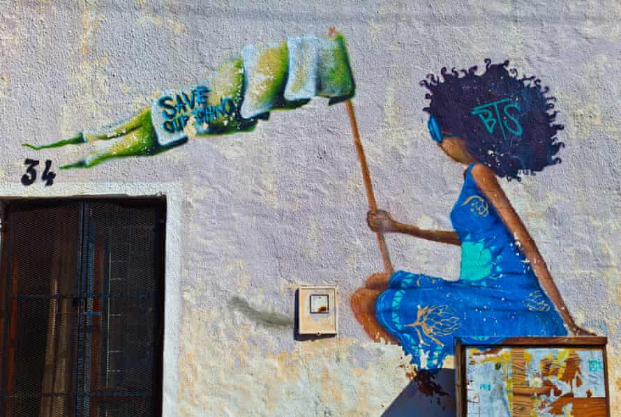 Urban art of Woodstock - Cape Town. On a wall of a house artwork depicts a girl in a blue dress with shades and a dark blue haircut holding a flag that reads Save our Rhino.