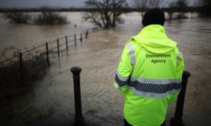 An Environment Agency employee looks at flood water from the river Arun, January 2014, in Pulborough, England.