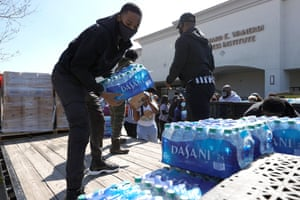 Volunteers stack cases of water during a water distribution event at the Fountain Life Center on in Houston, Texas.