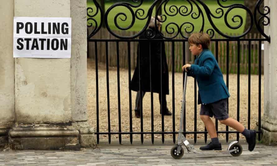 A boy scoots past a polling station sign in London