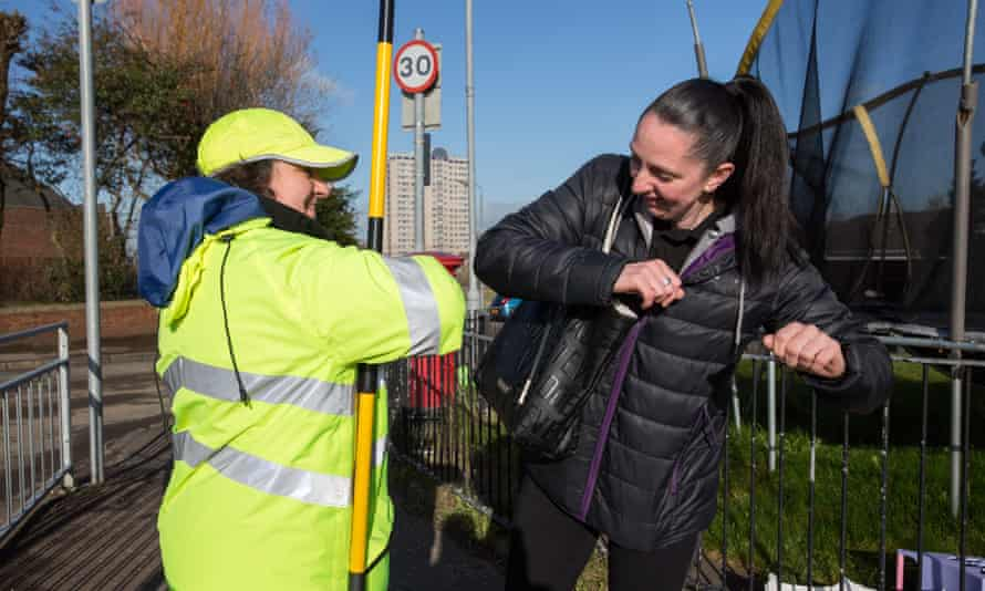 A lollipop lady does an elbow bump with a mother who has dropped her child off at school in Glasgow back in March just before full lockdown measure were imposed.