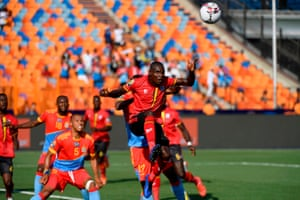 Uganda's forward Patrick Kaddu (right) heads the ball to score.