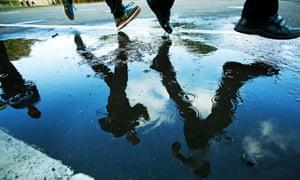 Children running in school playground, their legs reflected in rain puddle