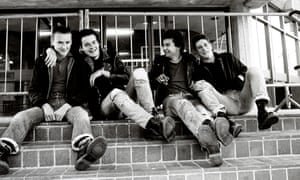 Black and white image of four young white men in leather jackets and ripped jeans sitting on steps smiling one with arm round the other.