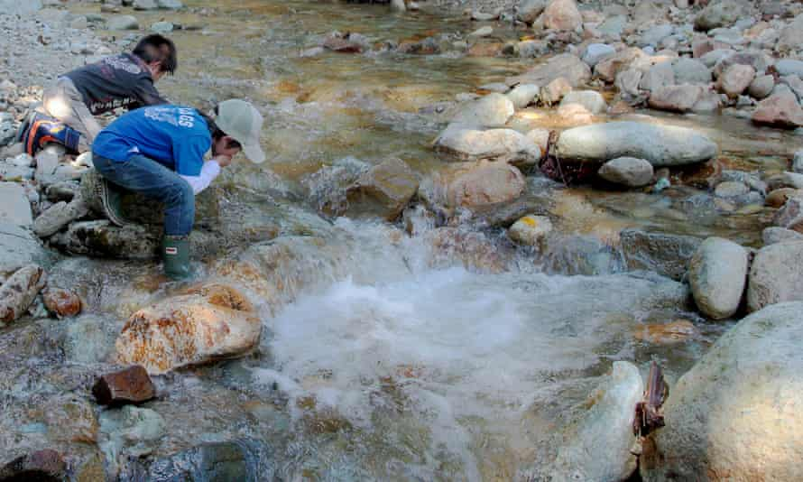 Sonoda's son and a friend drinking from a mountain stream before the disaster.