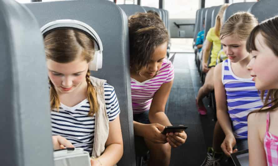 Schoolgirls using smart devices on a school bus