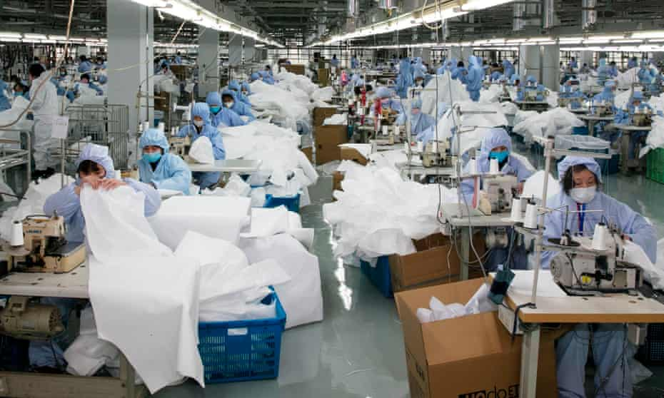 Workers produce protective clothing at a factory that previously produced suits and sportswear, in Wuxi in China's eastern Jiangsu province.