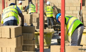 Construction workers building with bricks