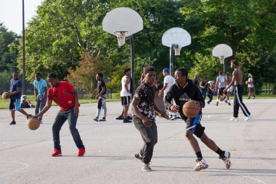 Teens play basketball in Ogden Park in the Englewood neighborhood in Chicago, Illinois.