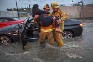 A firefighter carries a woman from her car after it was caught in street flooding in Sun Valley, California.