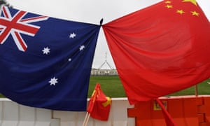 Parliament house is seen behind an Australian and a Chinese flag in Canberra.