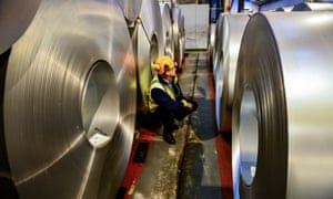 a manager stands among huge rolls of steel plate