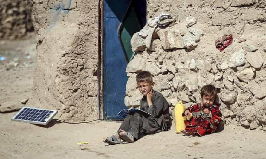 Two children read books in front of a door on the outskirts of Herat, Afghanistan on 15 October 2015.