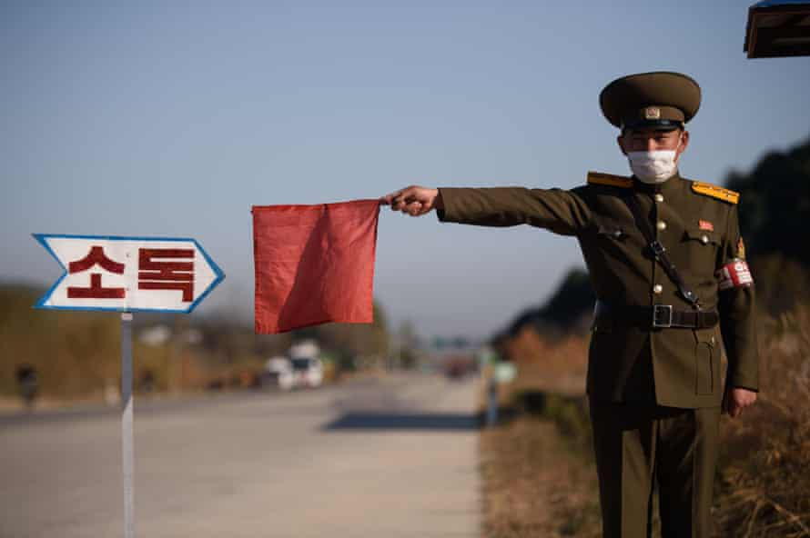 A security officer stops a taxi for disinfection outside Wonsan as Covid grips the country.