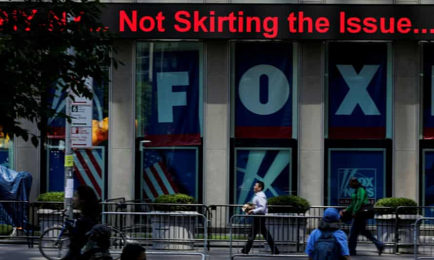 People pass by ads for Fox News on the News Corporation building in Manhattan.