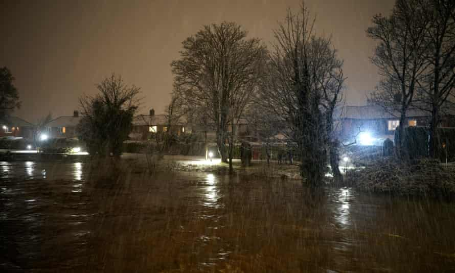 People look at the high water levels along the River Mersey, as severe flood warnings are issued and homes are evacuated.