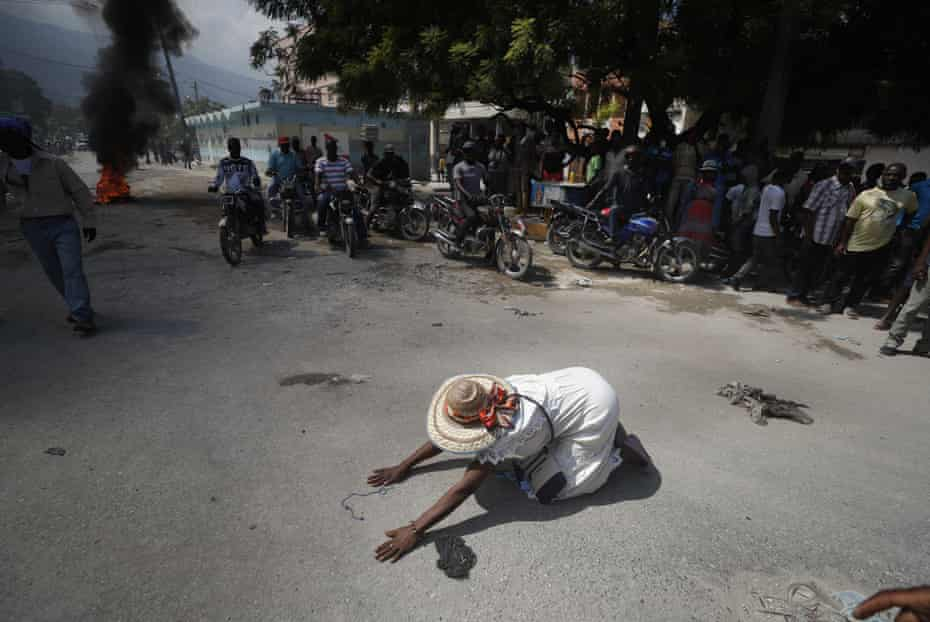A churchgoer prays in the street near burning tyres during a march called by religious leaders in Port-au-Prince, Haiti, 22 October