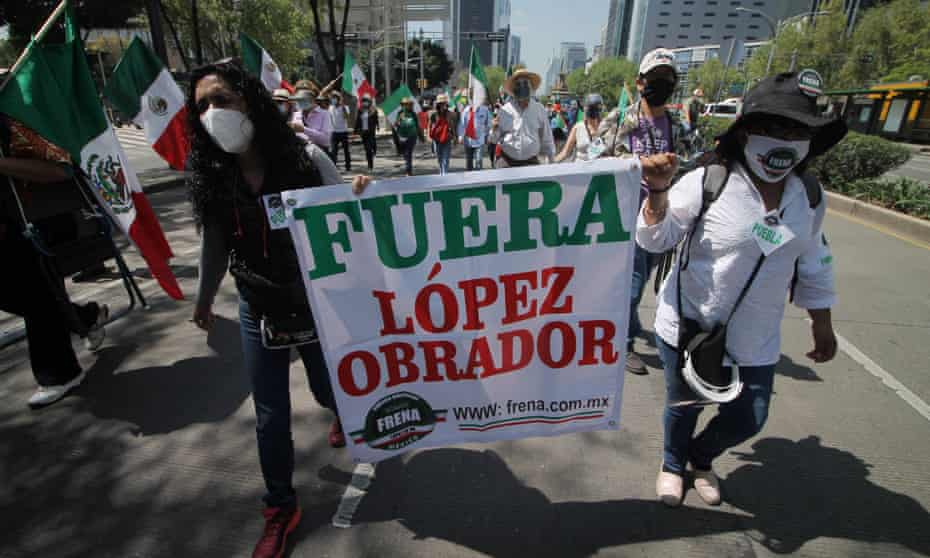 People carrying a banner saying 'López Obrador Out' march against President Amlo in Mexico City in October 2020.