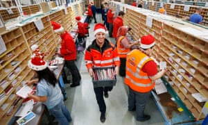 Santa-clad staff at Royal Mail's Glasgow mail centre sort sacks of largely secular Christmas cards.