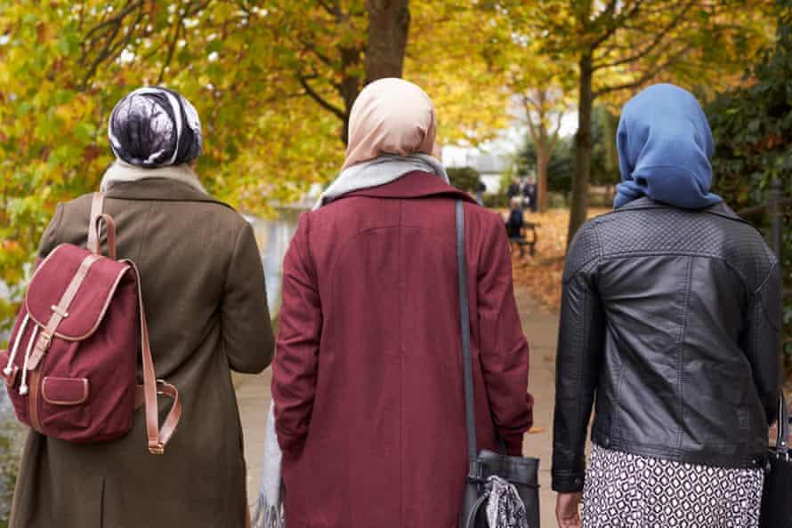 Three Muslim women walking on an autumn day, backs to camera