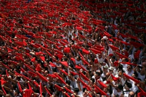 People hold up traditional red scarves during the start of the festival in Pamplona