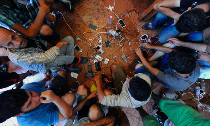 Migrants charge their mobile phones.