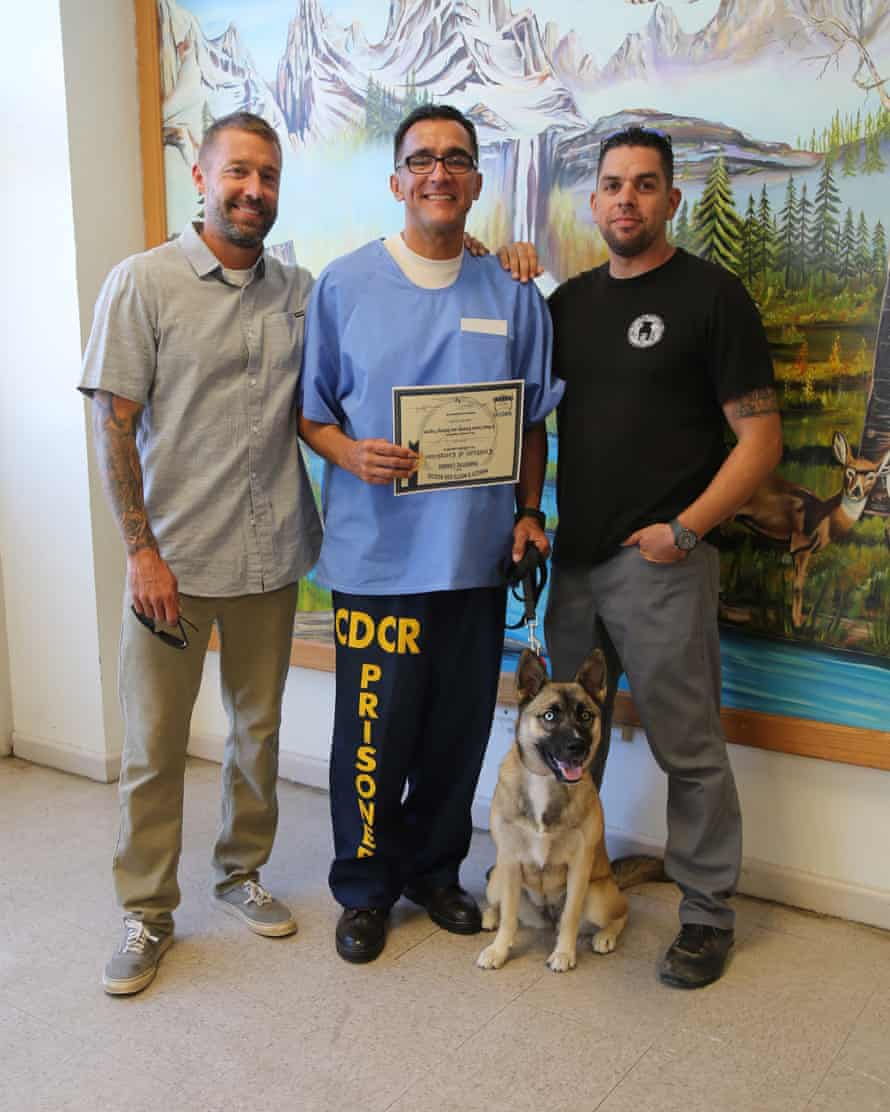 'I learned to be honest': (left) trainer Robert Villaneda and Pawsitive Change founder Zach Skow (right) with an inmate proudly showing his newly acquired trainer's certificate