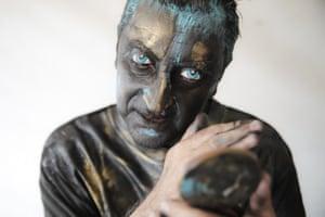 Portuguese artist Antonio Santos checks his makeup before his performance