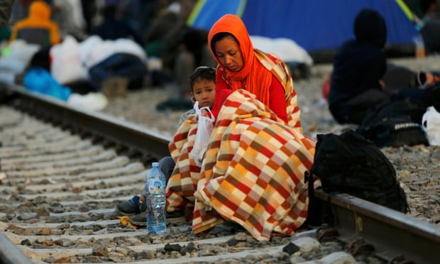 A woman and child use a blanket to keep warm as refugees gather on the tracks at the train station in Tovarnik, Croatia. Photograph: Antonio Bronic/Reuters
