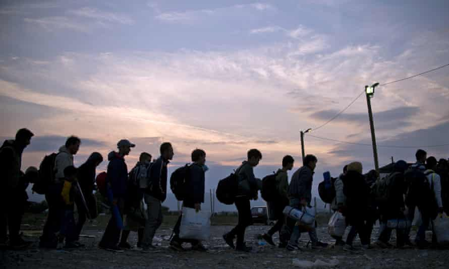 Migrants and refugees queue at a camp to be registered after crossing the Macedonian-Greek border near Gevgelija