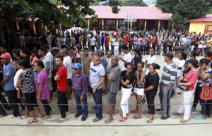 People queue up to vote at a polling station in Dili.