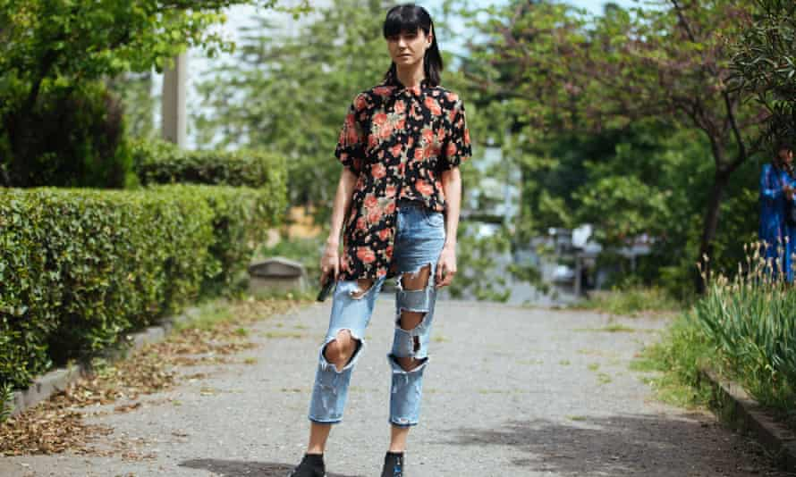 Model Likuna Metreveli wears a floral shirt half tucked into jeans with holes and black embellished sock sneakers