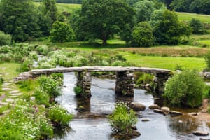 The historic clapper bridge over the East Dart River in Postbridge, Dartmoor, Devon, England, UK