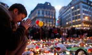 People attend a memorial near the old stock exchange in Brussels following Tuesday's bomb attacks
