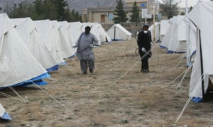 Workers with face masks spray the quarantine camp at Taftan near the border with Iran