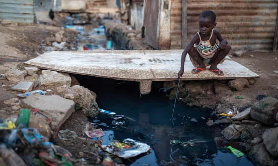 A young girl fishes waste out of a stream of sewage inside the Povoado slum in Luanda, Angola