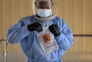 Divine Ayong seals a test in a biohazard bag after collecting a sample at The University of Texas at El Paso's Fox Fine Arts building.