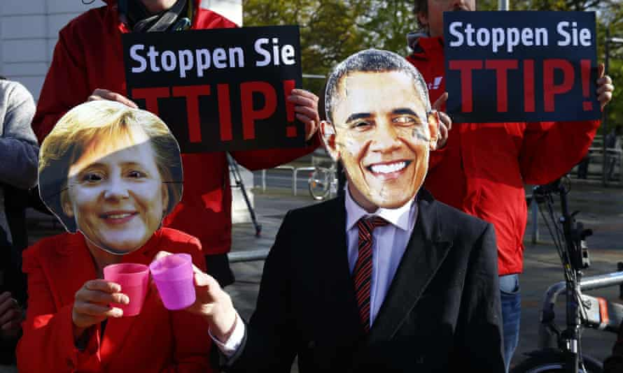 Protesters wear masks of Barack Obama and Angela Merkel as they demonstrate against TTIP free trade agreement