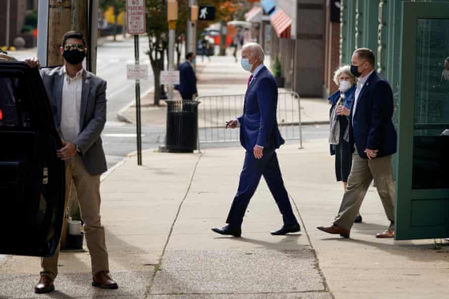 Joe Biden and Anita Dunn, center, wear masks as they leave the Queen theatre in Wilmington, Delaware on 19 October.