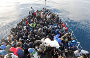 Mediterranean Sea Migrants sit in a boat after being rescued by Libyan coastguards