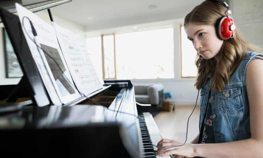Girl playing piano with headphones